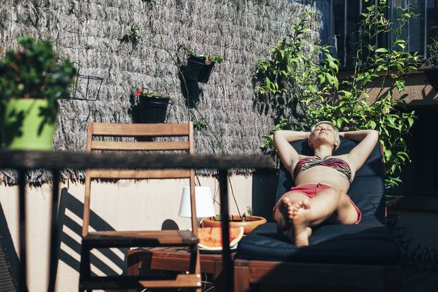 young woman sunbathing on deck chair on her terrace