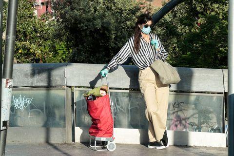 chica con una mascarilla y el carro de la compra