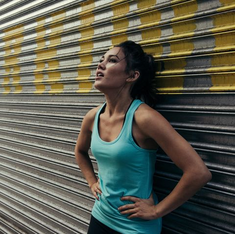 Young woman taking a break from running, against shutter