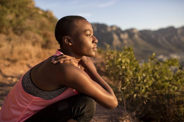 young woman taking a break on a hiking trip looking at view