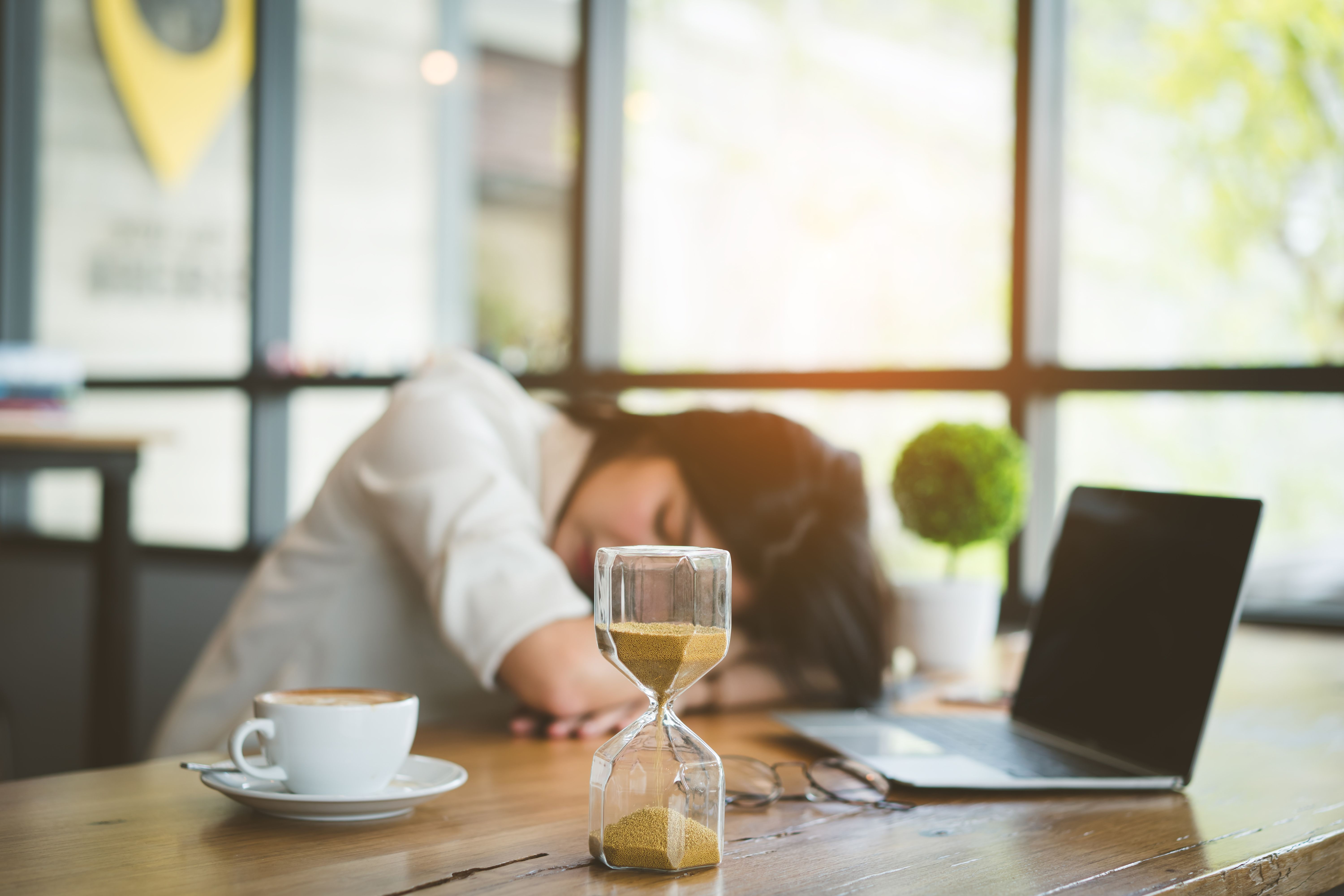 Young Woman Taking Nap By Laptop And Hourglass On Table In Cafe