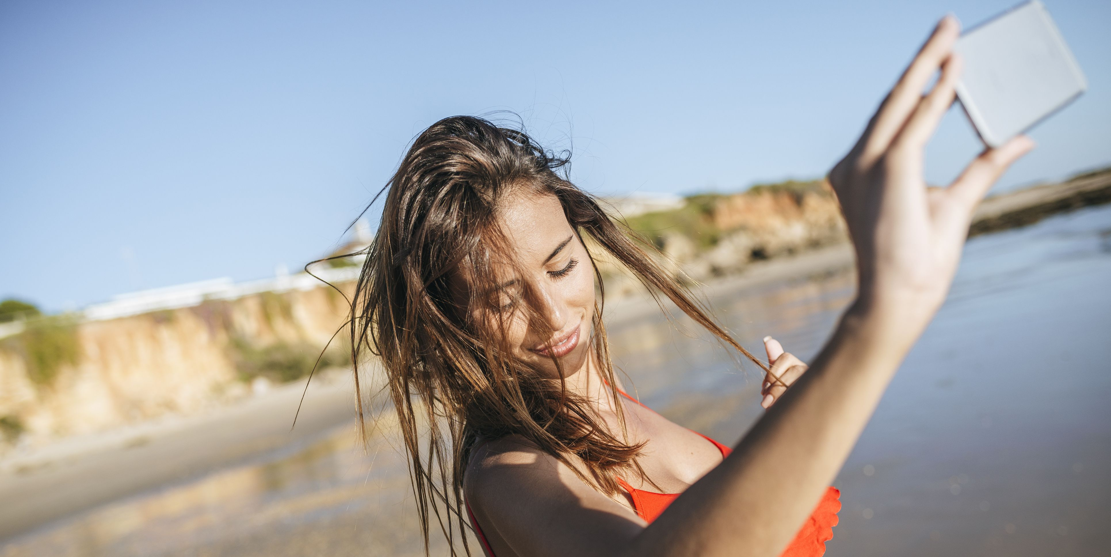 Young woman taking selfie on the beach with smartphone