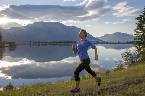 Young woman trail runner bounds along lakeshore in the mountain