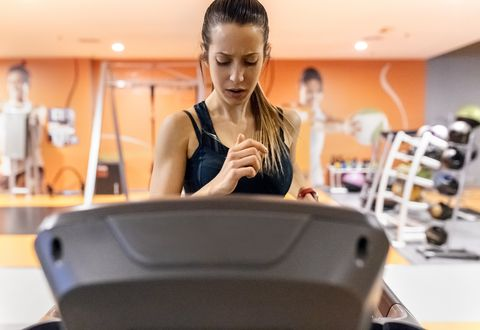 Young woman training in gym on a treadmil