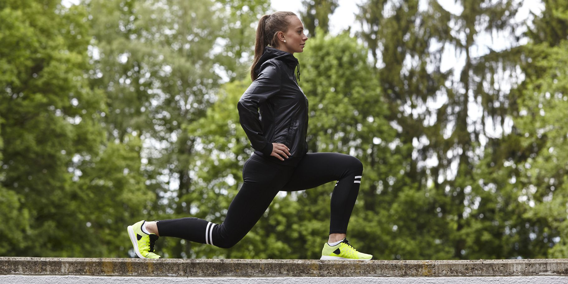 Young woman training, lunging on top of wall