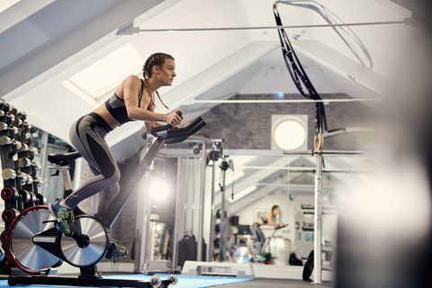 Young woman training, pedalling exercise bike in gym