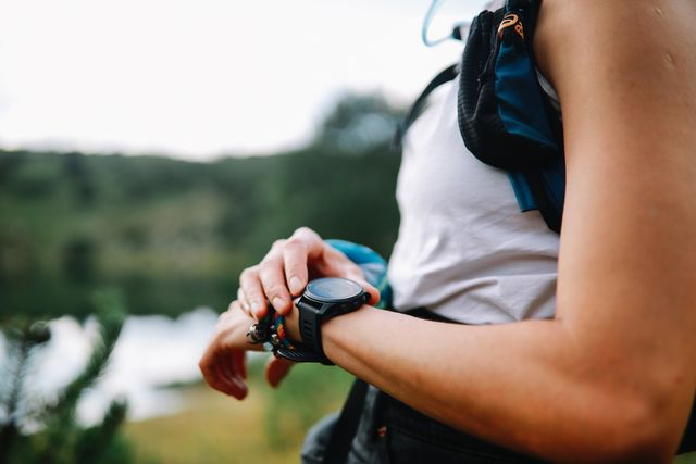 young woman using a smart watch during the hiking trip