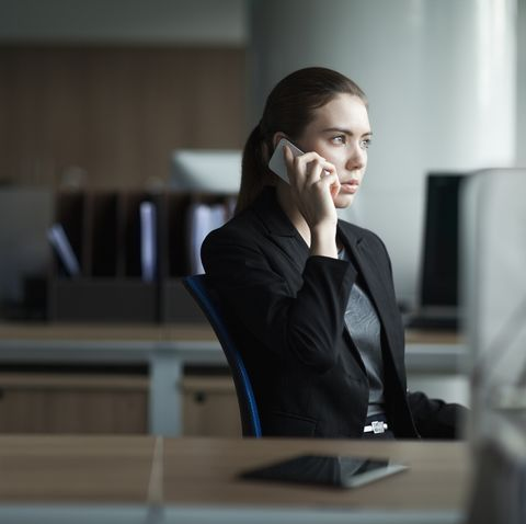 young woman using cell phone in business office