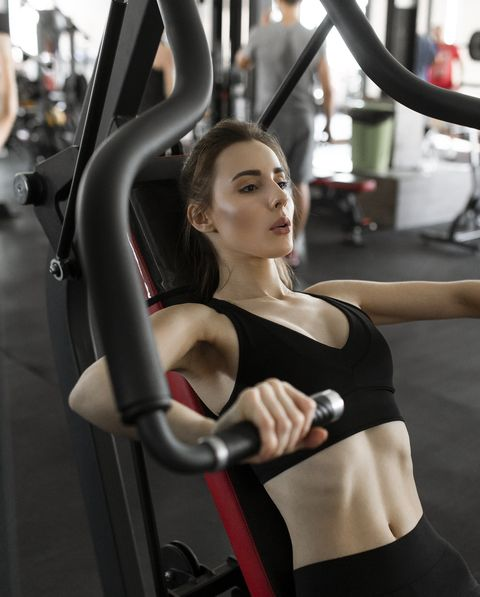 young woman using exercise machine in gym