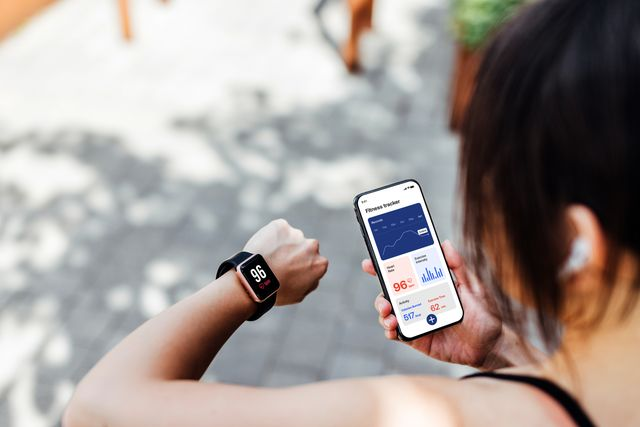 young woman using fitness tracker app on smart watch and smartphone