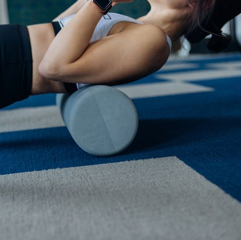 young woman using foam roller for stretching muscles