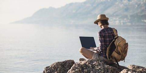 Young woman using laptop near the sea