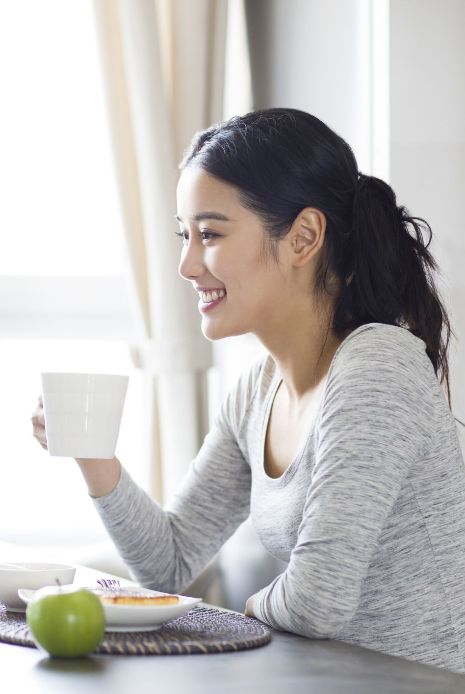 Young woman using laptop while having breakfast