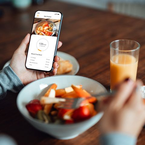 young woman using mobile app to track nutrition and count calories with smartphone