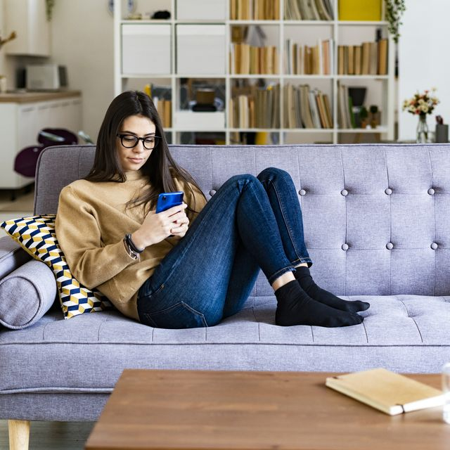 young woman using mobile phone while sitting resting on sofa at home