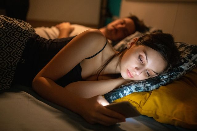 young woman using phone in bed by her boyfriend asleep