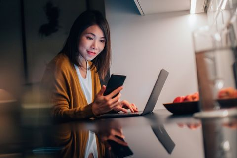 young woman using smartphone while working with laptop at home in the dark
