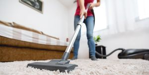 Young woman vacuuming house
