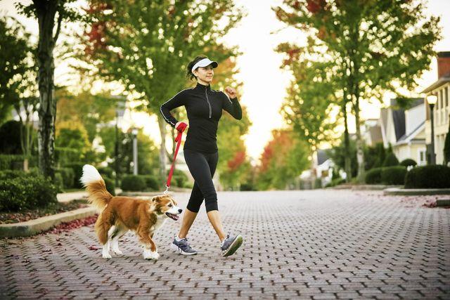 walking workouts for runners, young woman walking dog