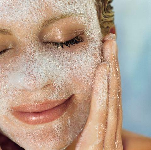 young woman washing face, close up
