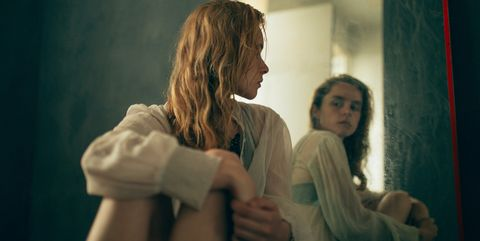 Young woman watching herself in the mirror