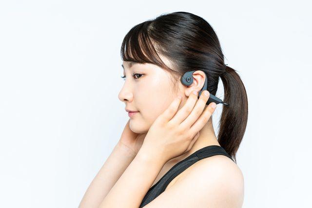 young woman wearing a bone conduction headphones
