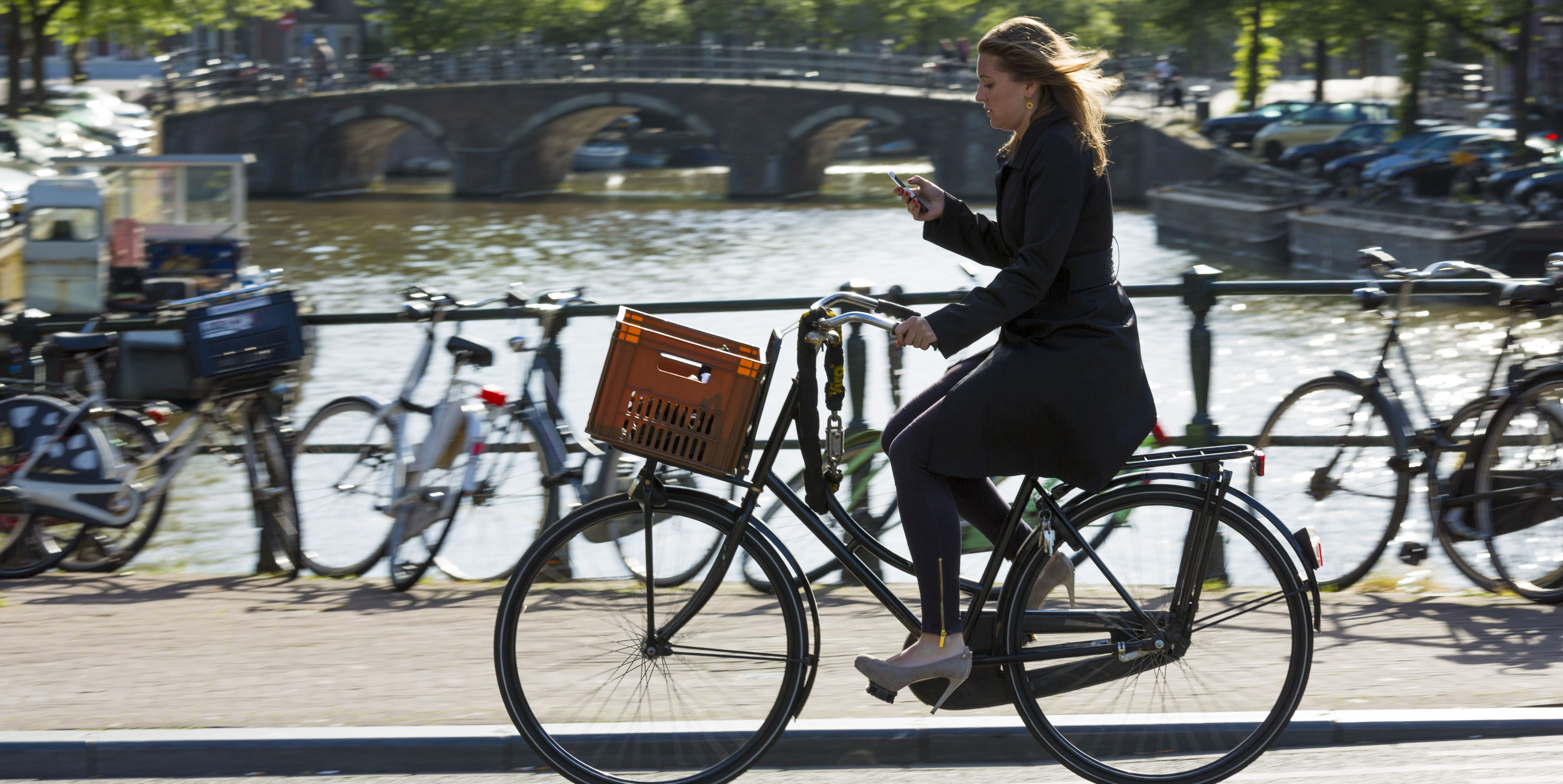 Young Woman Cycling on Bridge in Amsterdam, Holland