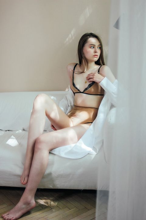 young woman wearing lingerie sitting on sofa at home
