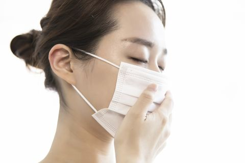 Young woman wearing protective face mask with cough