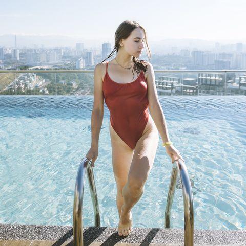 young woman wearing red swimsuit in rooftop swimming pool in kuala lumpur, malaysia