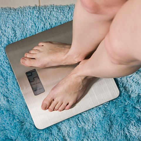 Young woman weighing herself on bathroom scales