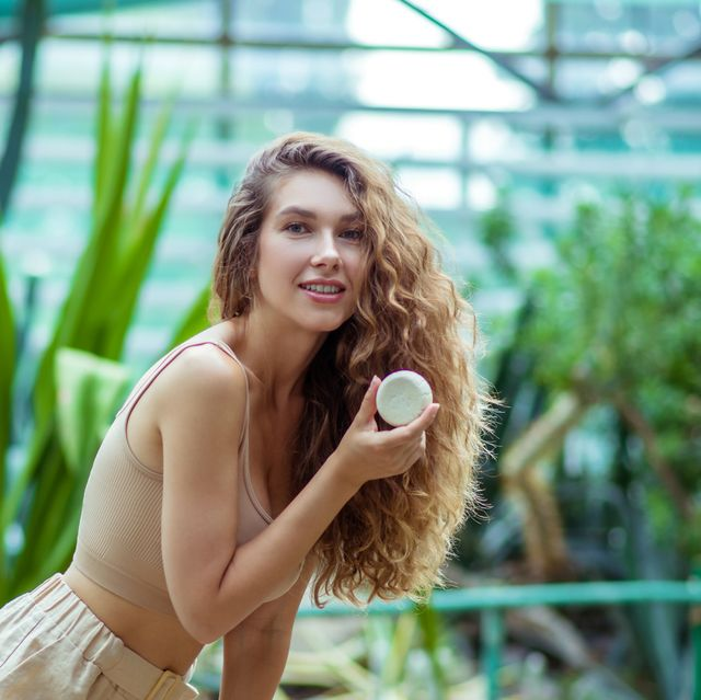 young woman with a bar of soap in a greehouse
