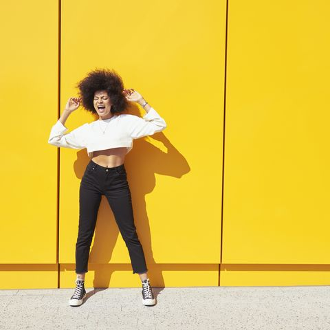 young woman with afro dancing in front of yellow wall