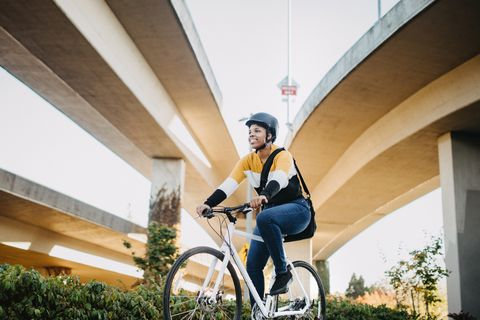 young woman with bike and messenger bag in the city