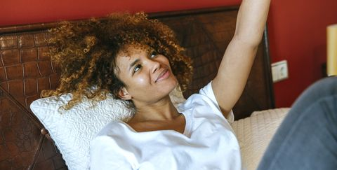 Young woman with curly hair lying in bed taking a selfie