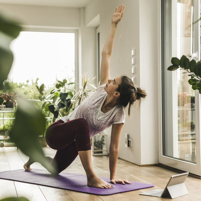 young woman with digital tablet exercising on mat at home
