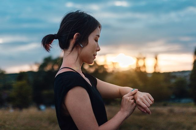 young woman with earphones and smart watch