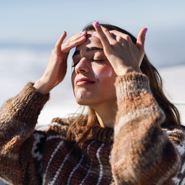 jonge vrouw brengt creme aan op gezicht in de zon