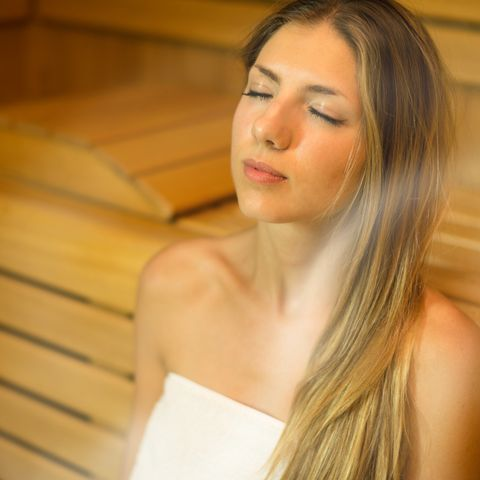 Young Woman With Eyes Closed Relaxing In Sauna Room