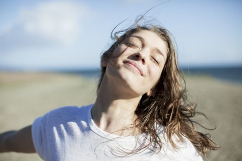 young woman with eyes closed smiling on a beach