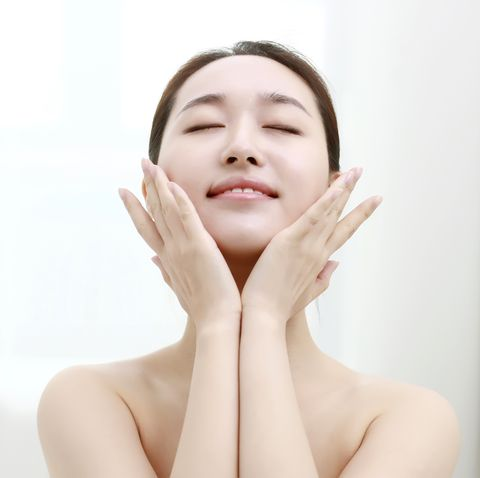 young woman with eyes closed touching face