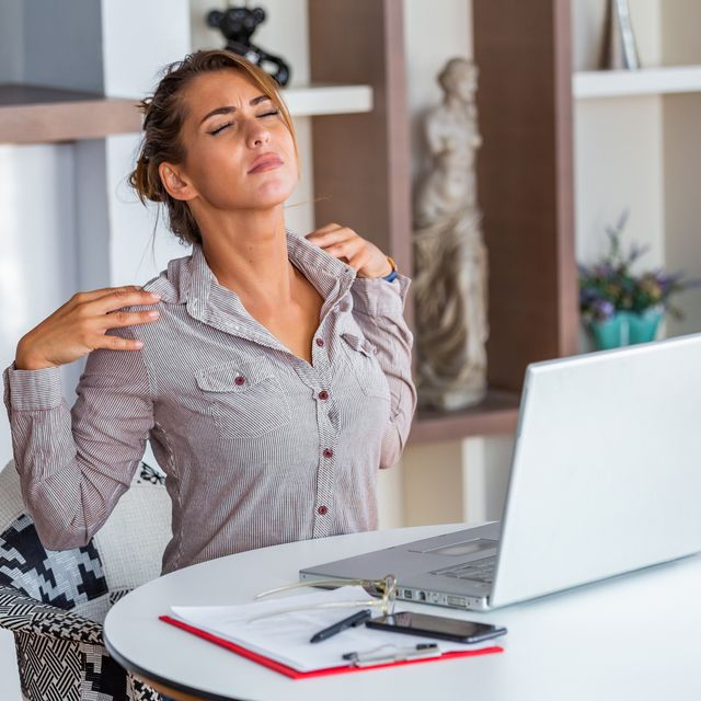 young woman with hands holding her shoulder pain office syndrome and health care concept business woman working with her laptop and with shoulder pain in the office