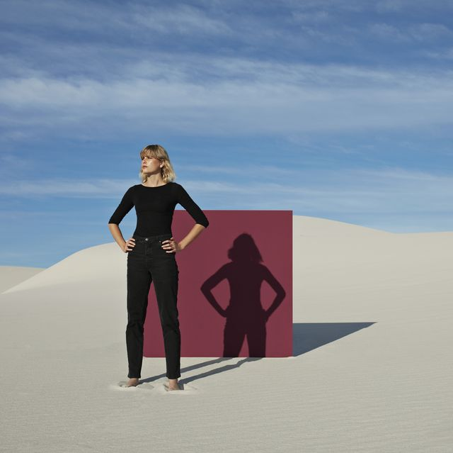 young woman with hands on hip standing against maroon portal at desert