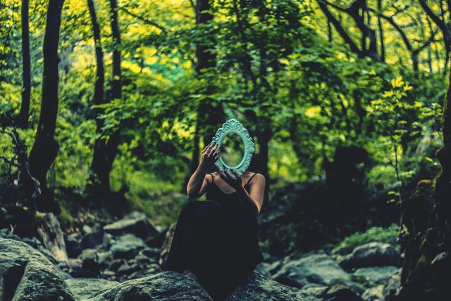 young woman with mirror in forest