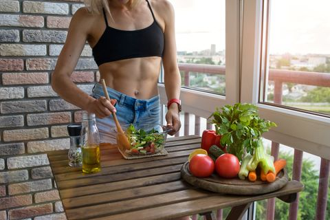young woman with perfect abdominals cooks food in a kitchen she has a muscular body and a diet food on his table