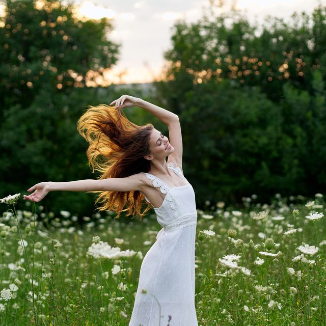 young woman with red hair in beautiful white dress outdoors
