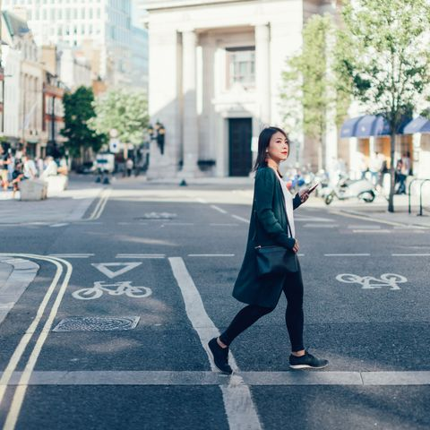 young woman with smart phone, crossing the road in the city