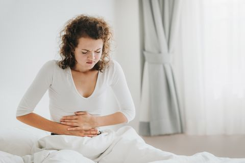 young woman with stomachache sitting on bed against wall at home