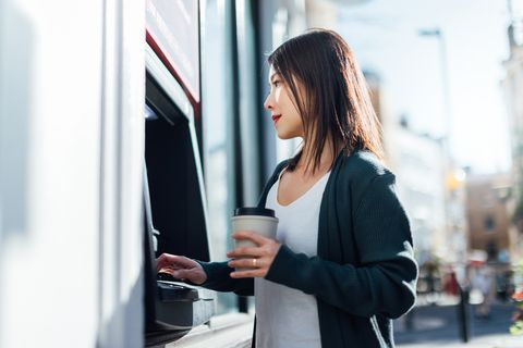 young woman withdrawing cash money at the atm