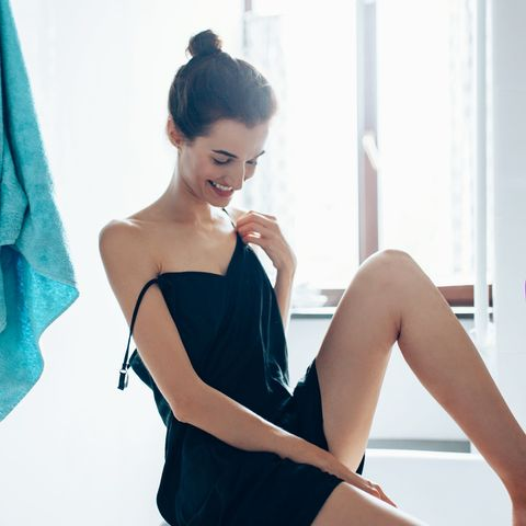 young woman woman feeling her smooth legs in the bathroom at home